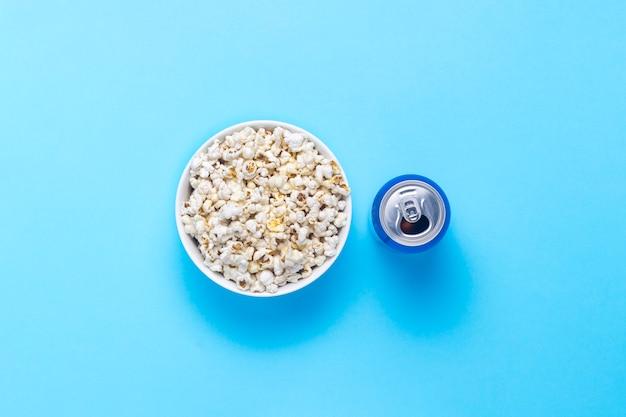 Ciotola con popcorn e una lattina di bevanda su uno sfondo blu. il concetto di guardare film e programmi tv preferiti, competizioni sportive. vista piana, vista dall'alto.