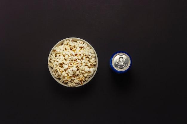 Ciotola con popcorn e una lattina di bevanda su uno sfondo nero. il concetto di guardare film e programmi tv preferiti, competizioni sportive. vista piana, vista dall'alto.