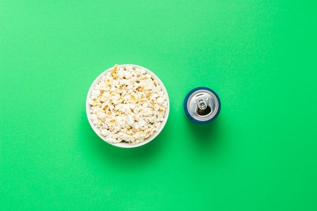 Ciotola con popcorn e una lattina di bevanda su uno sfondo verde. il concetto di guardare film e programmi tv preferiti, competizioni sportive. vista piana, vista dall'alto.