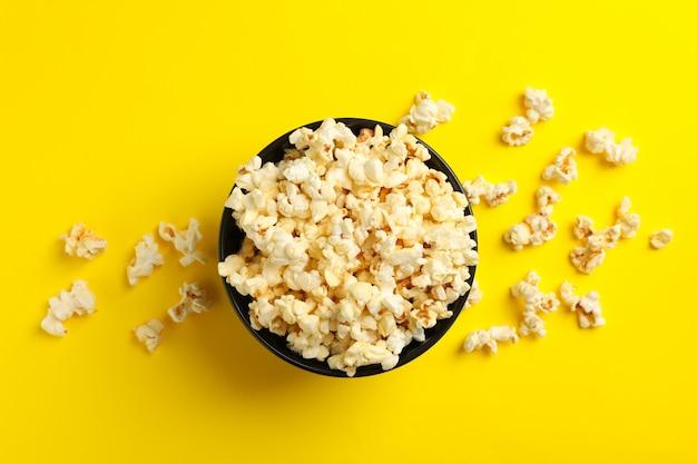 Ciotola con popcorn gustoso su spazio giallo. cibo per guardare il cinema