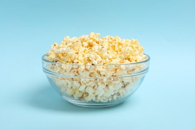 Ciotola con popcorn su spazio blu. cibo per guardare il cinema