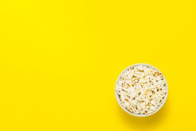 Ciotola con popcorn su uno sfondo giallo. vista piana, vista dall'alto.