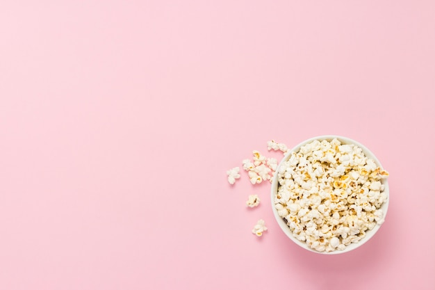 Ciotola con popcorn su uno sfondo rosa. vista piana, vista dall'alto.