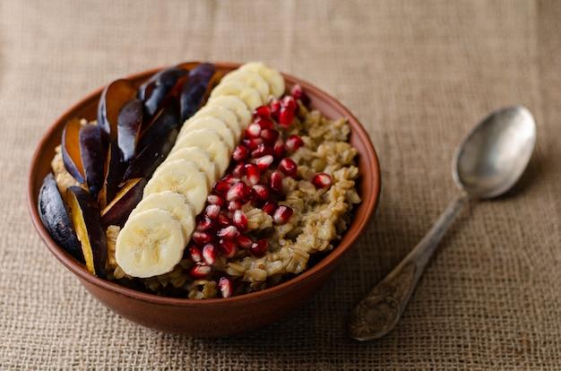 Ciotola con porridge di avena, banana, semi di melograno e prugna