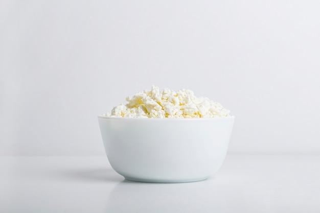 Ciotola con ricotta fatta in casa su uno sfondo bianco. concetto di prodotti lattiero-caseari sani con calcio. concetto di nutrizione