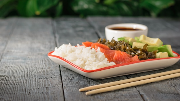 Ciotola con riso, avocado, alghe e salmone su un tavolo