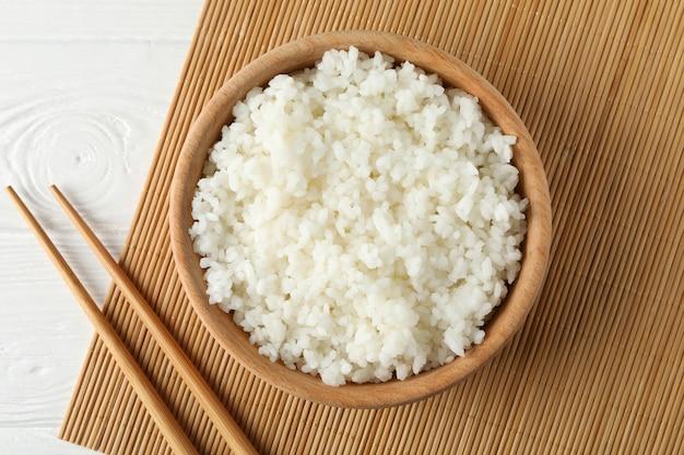 Ciotola con riso bollito e bacchette su superficie di legno