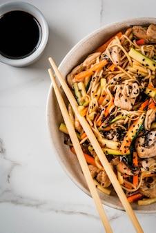 Ciotola con spaghetti di riso con salsa di soia e bacchette