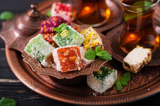 Ciotola con vari pezzi di lokum delizia turca e tè nero con menta su un tavolo scuro