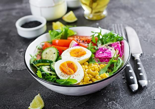 Ciotola con verdure crude fresche - cetriolo, pomodoro, anguria ravanello, lattuga, rucola, mais e uova sode