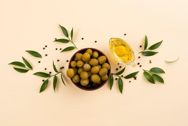 Ciotola dal design elegante con olive e bottiglia di olio