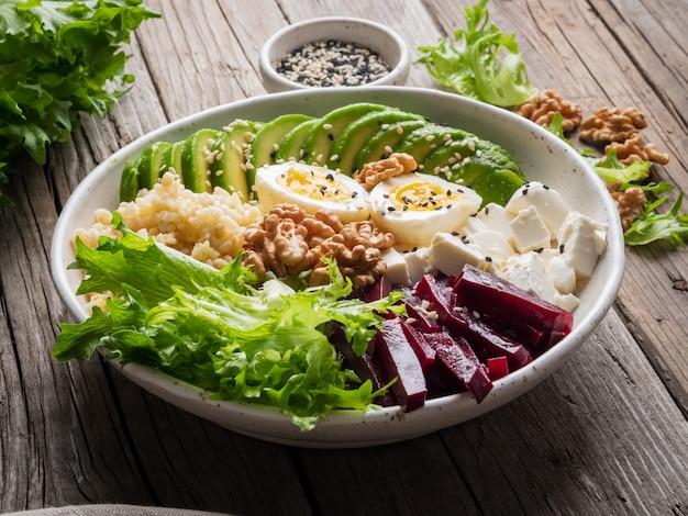 Ciotola del buddha, cibo bilanciato, menù vegetariano. vecchia tavola di legno scuro, vista laterale.