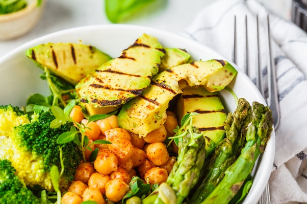 Ciotola del buddha con avocado alla griglia, asparagi, ceci, germogli di pisello e broccoli
