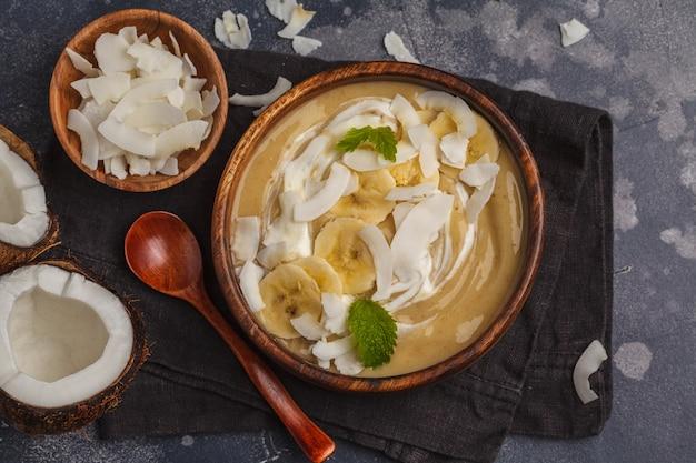 Ciotola del frullato della banana della noce di cocco in un piatto di legno su un fondo scuro, concetto sano dell'alimento del vegano. vista dall'alto, copia spazio.