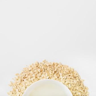 Ciotola del latte sopra i fiocchi di avena su fondo bianco