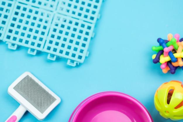 Ciotola dell'animale domestico e giocattolo di gomma sul fondo di colore. concetto di forniture per animali