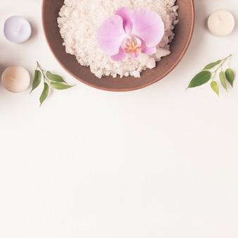 Ciotola dell'argilla con il sale marino del bagno un fiore dell'orchidea con le candele e il ramoscello sul contesto bianco