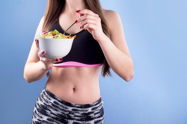 Ciotola della holding della donna con insalata di verdure