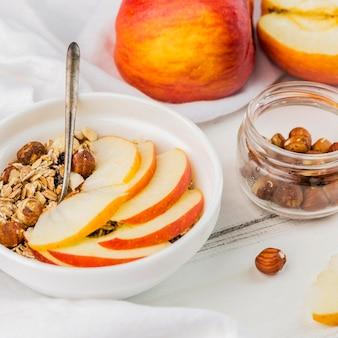Ciotola della prima colazione del primo piano con la mela e il granola