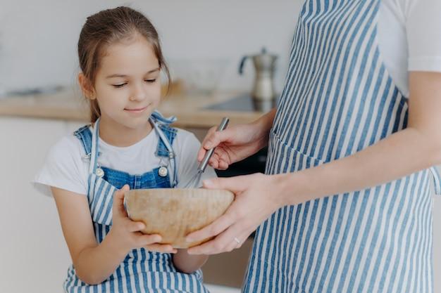 Ciotola della stretta della bambina occupata, guarda come la madre sbatte gli ingredienti, impara a cucinare
