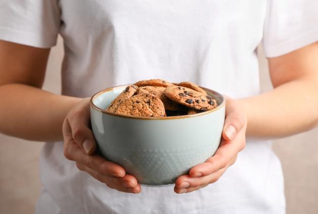 Ciotola della tenuta della donna con i biscotti di pepita di cioccolato saporiti, primo piano