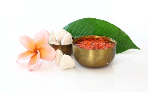 Ciotola di acqua, fiori e argilla su bianco per il festival di songkran