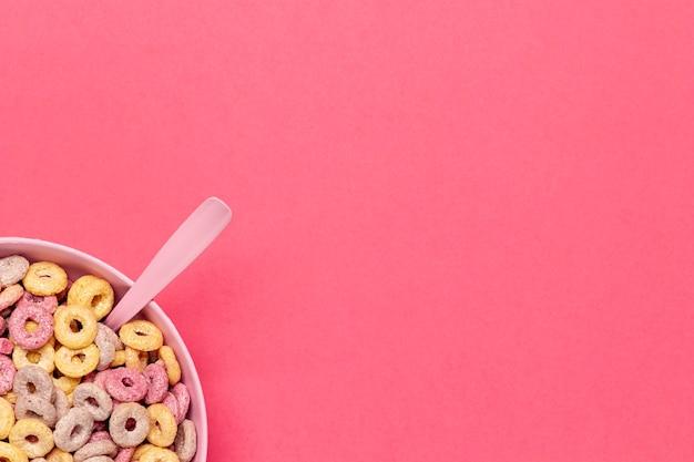 Ciotola di anelli di frutta cereali con cucchiaio nell'angolo
