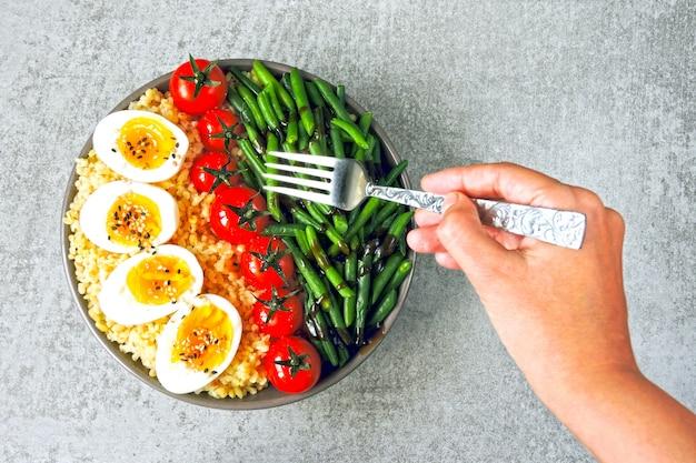 Ciotola di buddha con bulgur, fagiolini, pomodorini e metà dell'uovo sodo. cibo sano in una ciotola. il concetto di nutrizione dietetica.