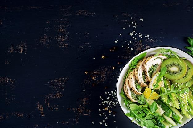 Ciotola di buddha con filetto di pollo, avocado, cetriolo, rucola fresca e sesamo. detox e concetto sano della ciotola di dieta di cheto. vista dall'alto, vista dall'alto, disteso, copia spazio