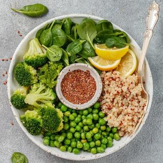 Ciotola di buddha. quinoa con broccoli, spinaci, piselli, limone e semi di lino con olio d'oliva