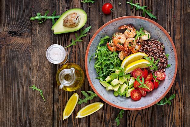Ciotola di buddha sano delizioso con gamberetti, pomodoro, avocado, quinoa, limone e rucola sul tavolo di legno. cibo salutare. vista dall'alto. disteso.