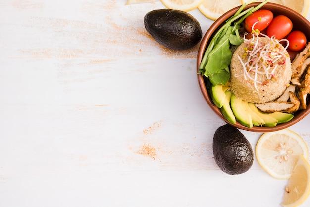 Ciotola di burrito con pollo; spinaci; pomodoro; fette di avocado e limone in ciotola sul contesto strutturato in legno bianco
