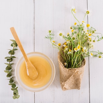 Ciotola di cagliata di limone e bei fiori della camomilla su fondo di legno