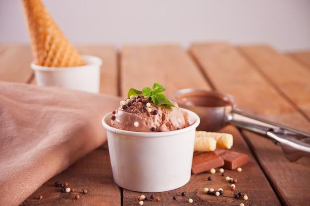 Ciotola di carta di gelato al cioccolato, cono di cialda e cucchiaio per gelato
