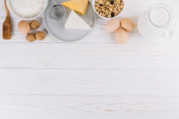 Ciotola di cereali; latte; uova; formaggio; farina e noci sul tavolo di legno bianco