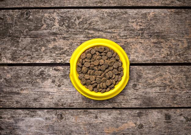 Ciotola di cibo per cani secco sul pavimento di legno