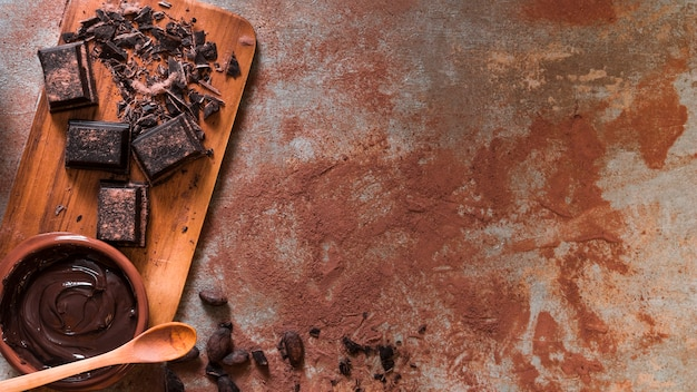 Ciotola di cioccolato fuso e barra schiacciata sul tagliere con cucchiaio di legno