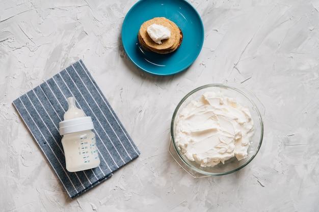 Ciotola di crema di formaggio fatto in casa in lastra di vetro con frittelle e ricotta vista dall'alto cibo sano
