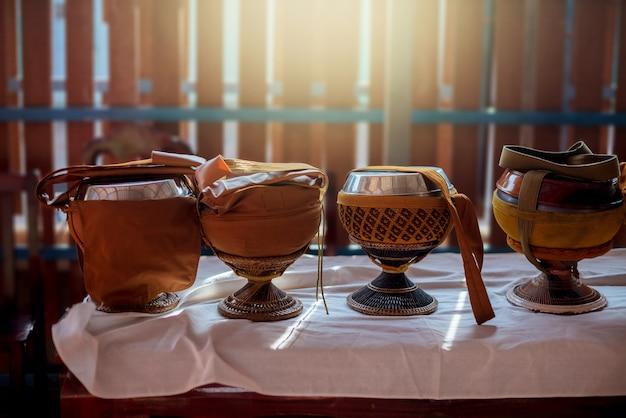 Ciotola di elemosina del monaco sul tavolo con illuminazione.