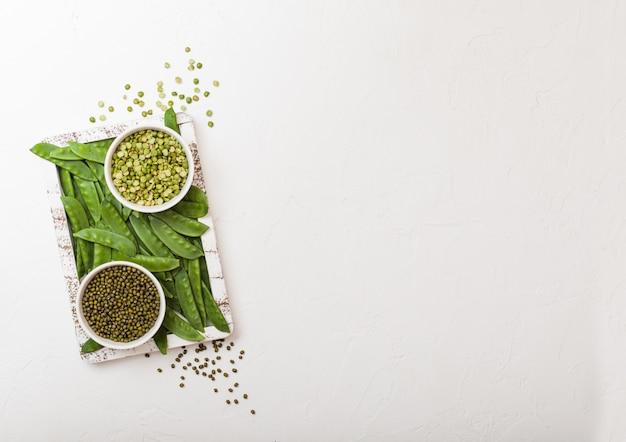 Ciotola di fagioli verdi e di peaswith divinità organica cruda in scatola di legno d'annata sul backround bianco della cucina