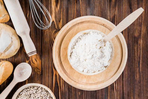 Ciotola di farina bianca sul piatto di legno sopra il tavolo