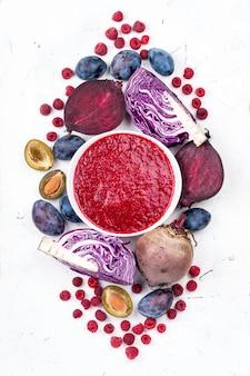 Ciotola di frullati con frutta e verdure viola su priorità bassa bianca