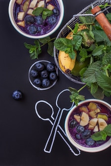Ciotola di frullati con frutti di bosco su una lavagna con cucchiai