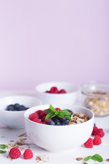 Ciotola di frullato con yogurt, frutti di bosco freschi e cereali. superfood