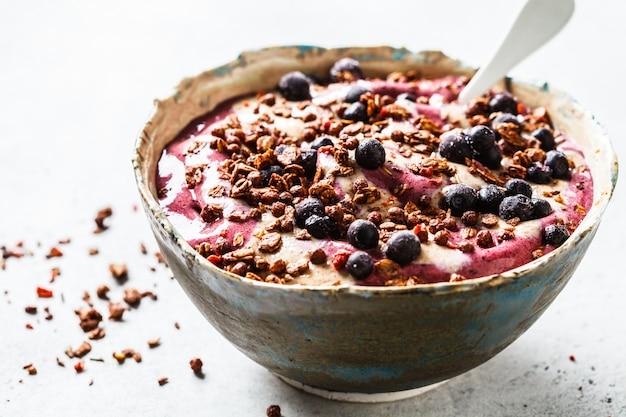 Ciotola di frullato di bacche con burro di arachidi e muesli. concetto di cibo sano vegan.