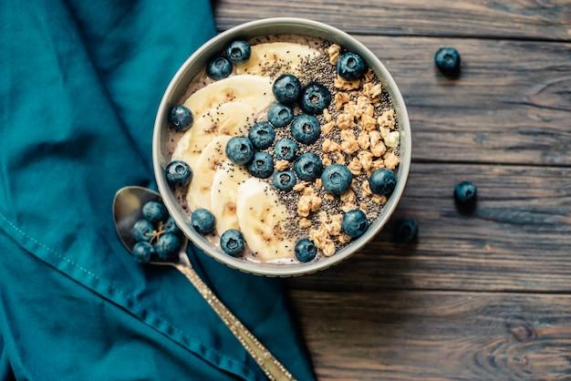 Ciotola di frullato di bacche di colazione sana condita con banana, muesli, mirtilli e semi di chia
