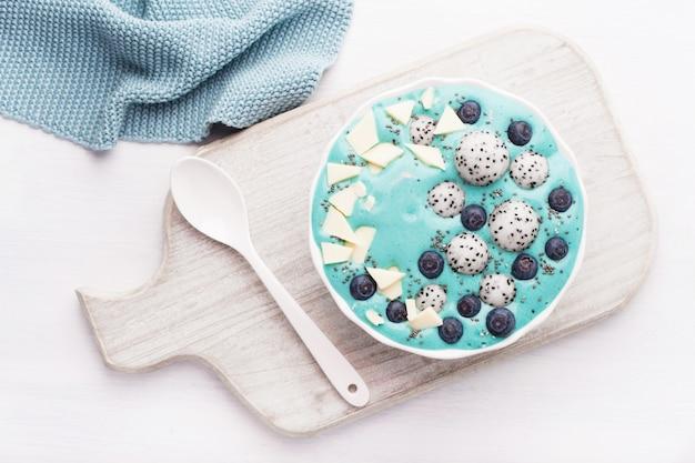 Ciotola di frullato di spirulina blu sano con mirtillo, cioccolata bianca, frutta del drago e semi di chia