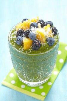 Ciotola di frullato verde colazione condita con frutta