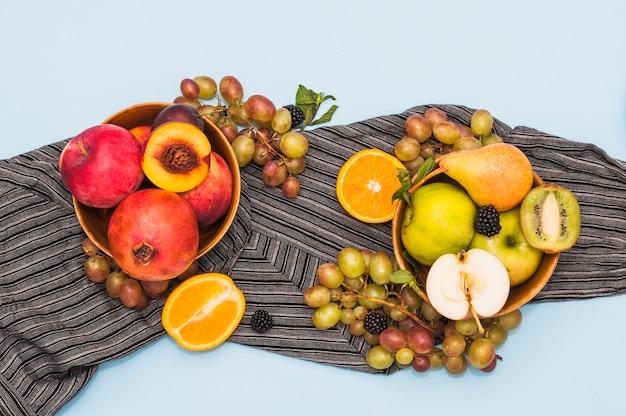 Ciotola di frutta e uva sul tessile su sfondo blu