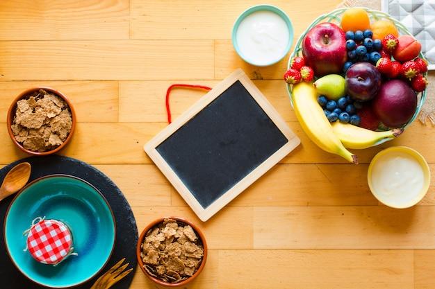 Ciotola di frutta fresca con banana, mela, fragole, albicocche, mirtilli, prugne, cereali integrali, forchette, vista dall'alto